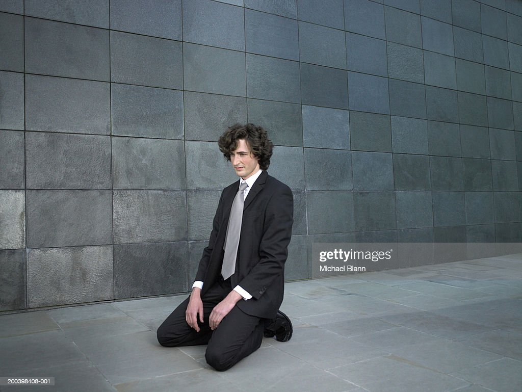 Young businessman kneeling on pavement : Stock Photo