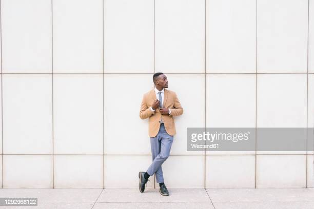 young businessman leaning against a wall looking sideways - menswear stock pictures, royalty-free photos & images