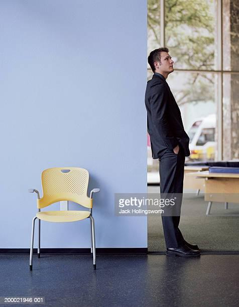 young businessman leaning against wall, hands in pockets, profile - appoggiarsi foto e immagini stock