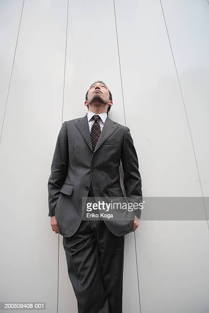 Young businessman leaning against wall, looking up, low angle view