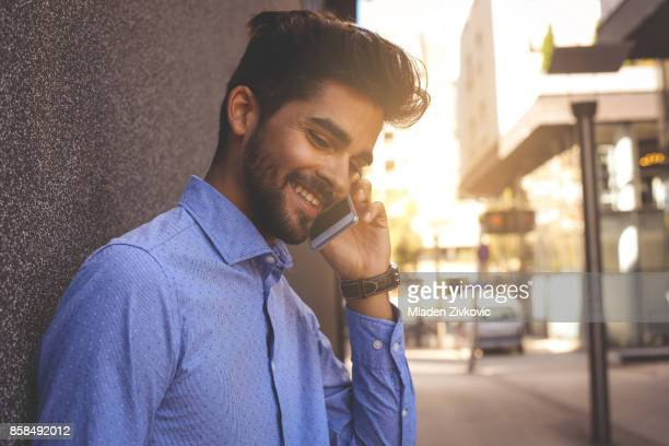 Young businessman leaning against wall talking on smart phone. Space for copy.