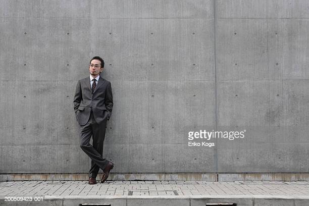 Young businessman leaning against wall, with hands in pockets
