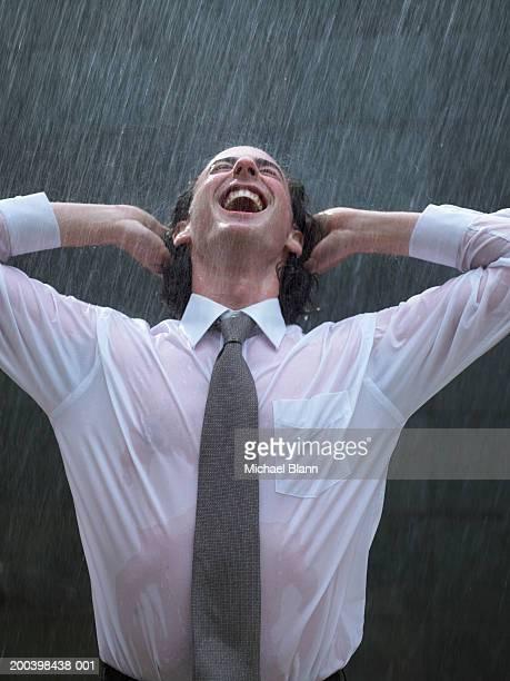 Jeune homme d'affaires s'appuyant derrière sous la pluie, les mains derrière la tête, rire