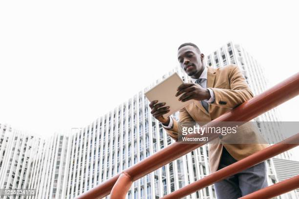 young businessman leaning on a railing in the city using a tablet - menswear stock pictures, royalty-free photos & images