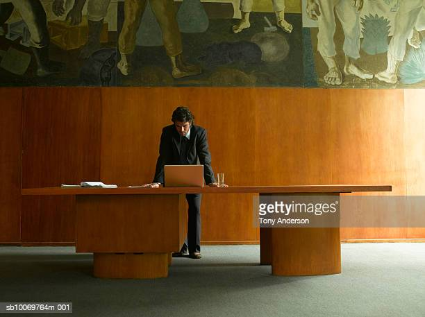 Young businessman leaning on desk looking down at laptop