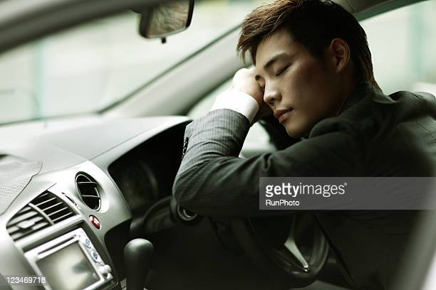 young businessman leaning on the handle of the car