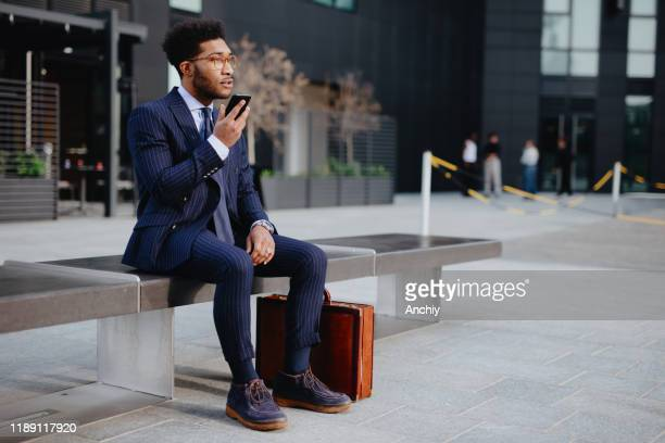 young businessman leaving voice messages to his colleague - financial analyst stock pictures, royalty-free photos & images