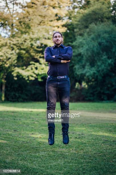 young businessman levitating in park - hovering stock pictures, royalty-free photos & images