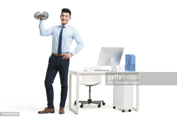 Young businessman lifting weights in office