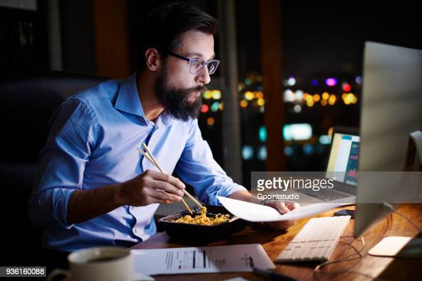 Young businessman looking at computer and eating takeaway at office desk at night