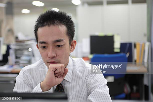 Young businessman looking at computer monitor in office, close-up