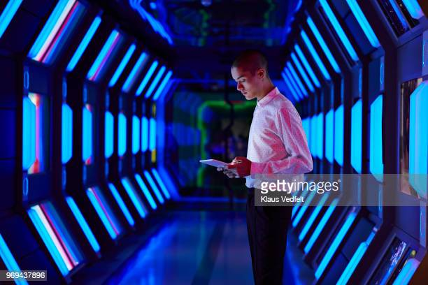 young businessman looking at digital tablet in spaceship like corridor - security stock pictures, royalty-free photos & images