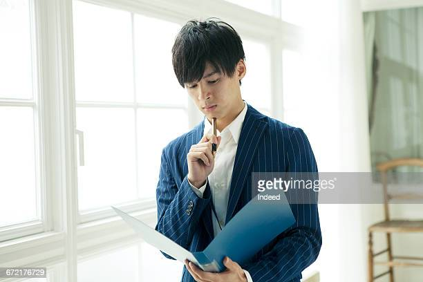 young businessman looking at file - 下を向く ストックフォトと画像