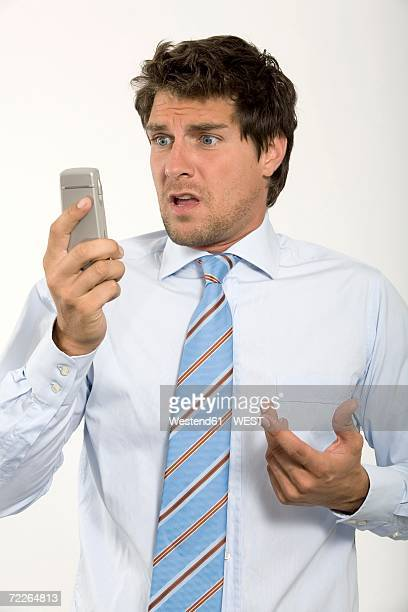 Young businessman looking at mobile phone, close-up