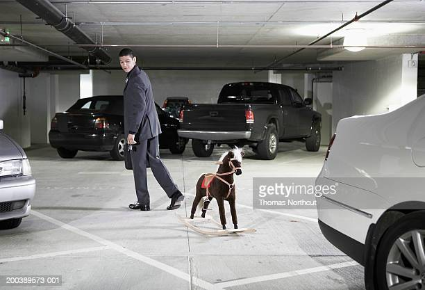 Young businessman looking at rocking horse in parking garage