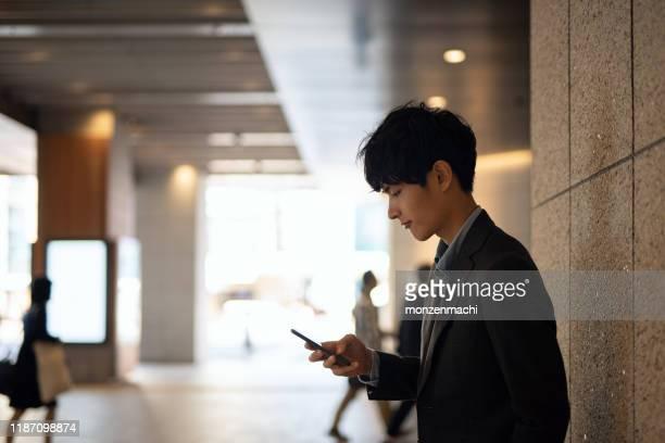 歩行者歩道でスマートフォンを見ている若いビジネスマン - 待つ ストックフォトと画像