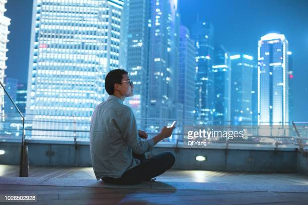 young businessman looking at smartphone on the roof - man city stock photos and pictures