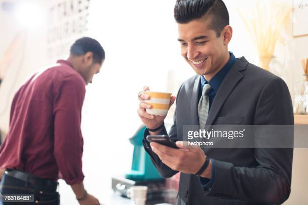 young businessman looking at smartphone - heshphoto stockfoto's en -beelden