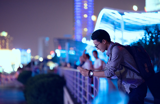 Young businessman looking at smartphone, Shanghai, China - gettyimageskorea