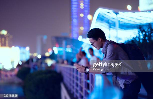 Young businessman looking at smartphone, Shanghai, China