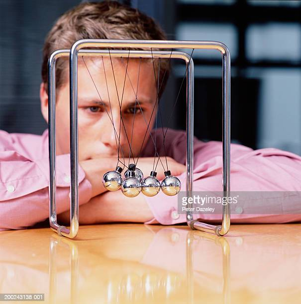 Young businessman looking at tangled Newton's Cradle, close-up