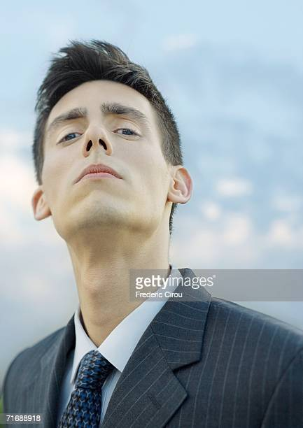 young businessman, looking down at camera, portrait - head back stock pictures, royalty-free photos & images