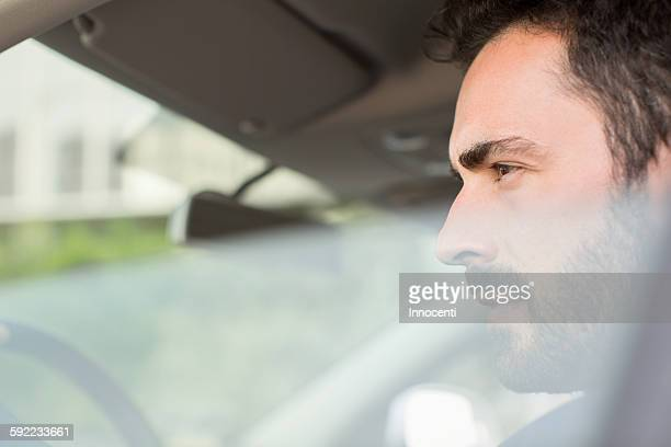 Young businessman looking from car window