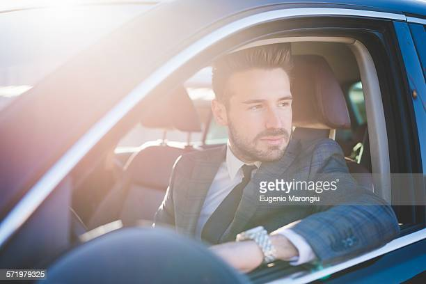 Young businessman looking out from car window