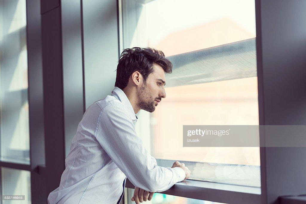 Giovane uomo d'affari guardando fuori la finestra : Foto stock