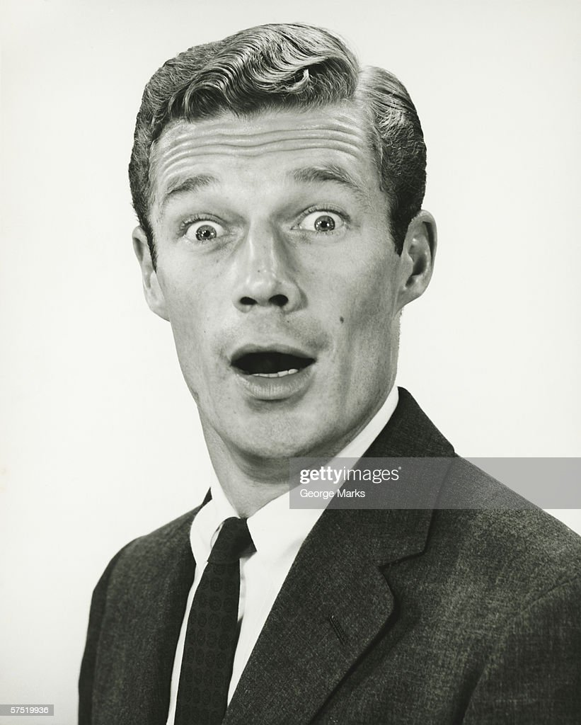 Young businessman looking surprised, posing in studio, (B&W), portrait : Stock Photo