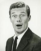 Young businessman looking surprised, posing in studio, (B&W), portrait