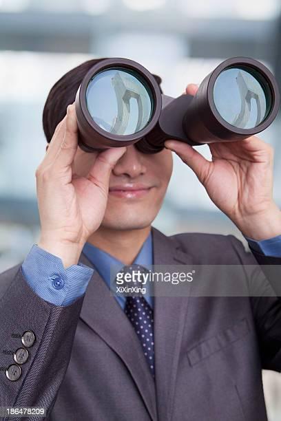 Young businessman looking through binoculars, Beijing