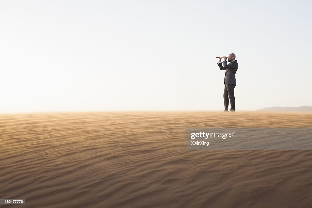 Young businessman looking through telescope in  the middle of the desert : Stock Photo