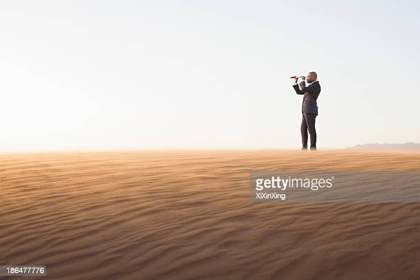 Young businessman looking through telescope in  the middle of the desert