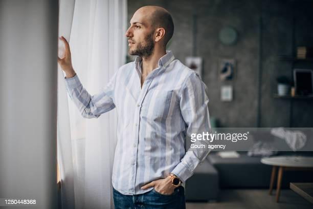 jeune homme d'affaires regardant par la fenêtre - homme chauve photos et images de collection
