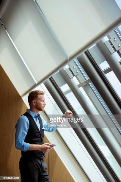 Jeune homme d'affaires, regardant par la fenêtre