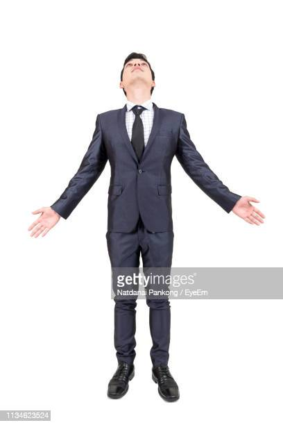 young businessman looking up while standing against white background - arms outstretched stock pictures, royalty-free photos & images