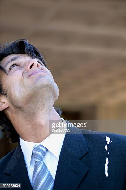 Young businessman looking up with bird dropping on his suit