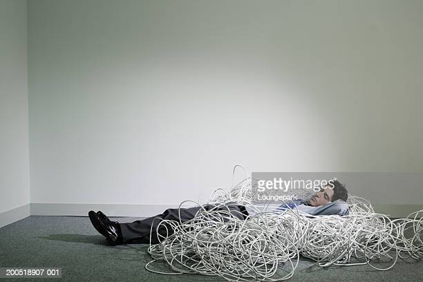 Young businessman lying on cables on floor