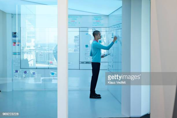 young businessman making notes on whiteboard - light blue stock pictures, royalty-free photos & images