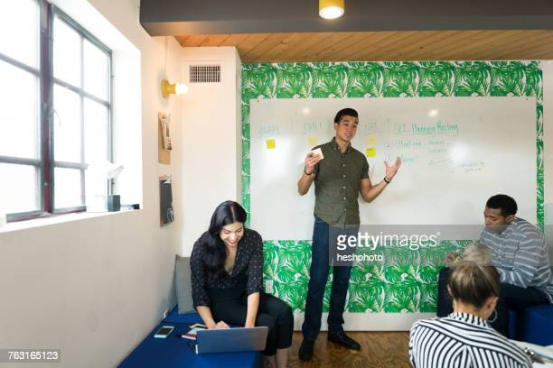 young businessman making presentation in creative meeting room - heshphoto photos et images de collection