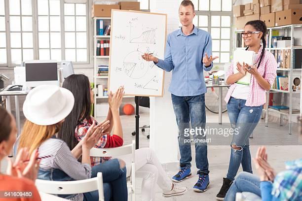 Jeune homme d'affaires faire une présentation devant ses collègues