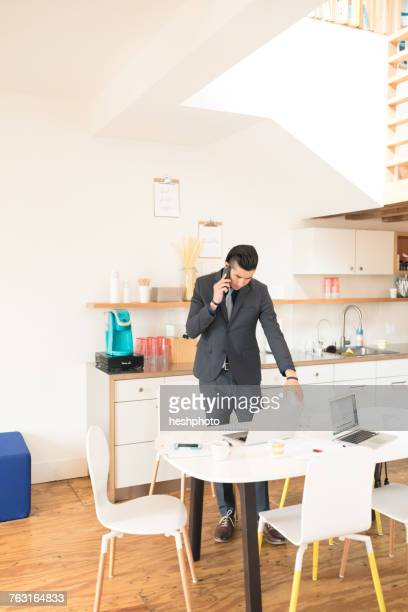 young businessman making smartphone call at office table - heshphoto photos et images de collection