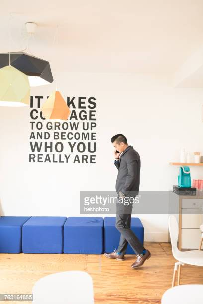 young businessman making smartphone call in creative office - heshphoto stock pictures, royalty-free photos & images