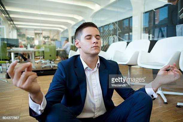 Young businessman meditating in office