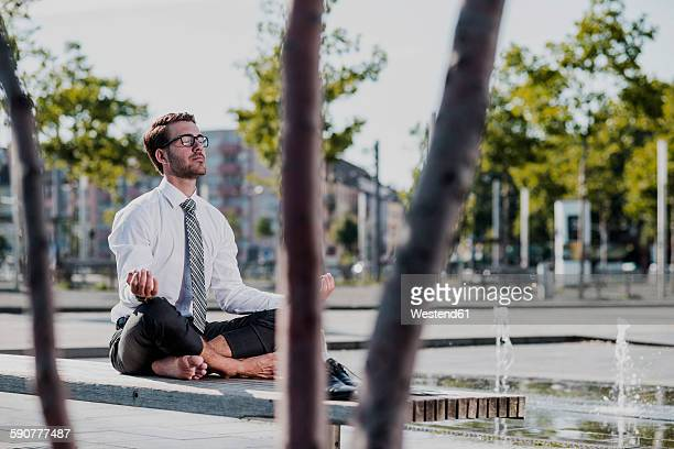Young businessman meditating on bench