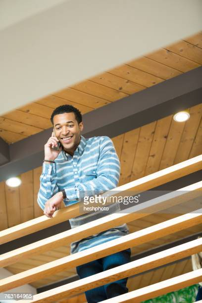 young businessman on balcony making smartphone call - heshphoto stock pictures, royalty-free photos & images