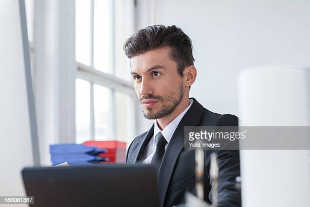 Young businessman on his desk working with laptop