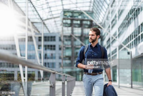 young businessman on the go at building with glass facade - arrival photos stock photos and pictures