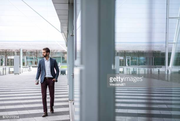 young businessman on the go at building with glass facade - businesswear stock pictures, royalty-free photos & images